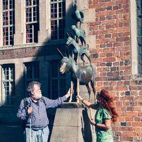 Die Bronze der Bremer Stadtmusikanten: Ein Mann und eine Frau umfassen die Vorderbeine des Esels, da dies Glück bringen soll.