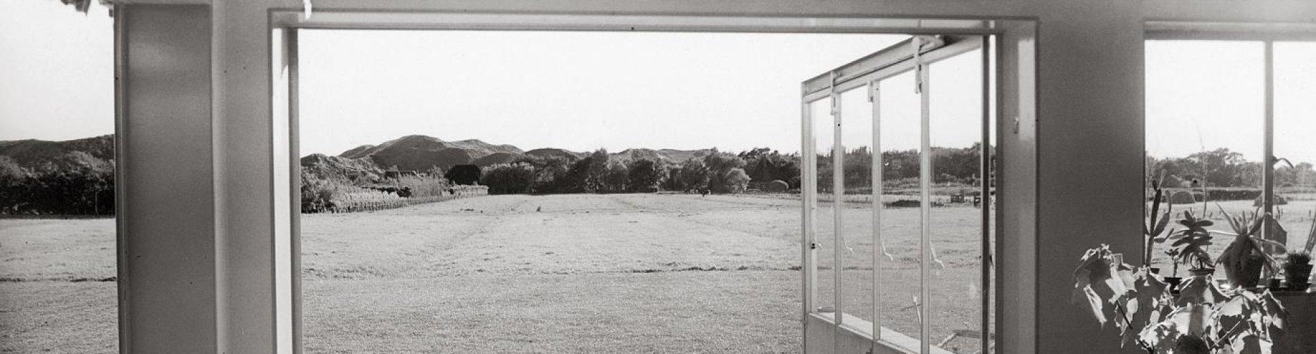 Eine Schwarz-Weiß-Aufnahme von Eva Besnyö. Zu sehen ist der Blick in den Garten eines Sommerhauses.