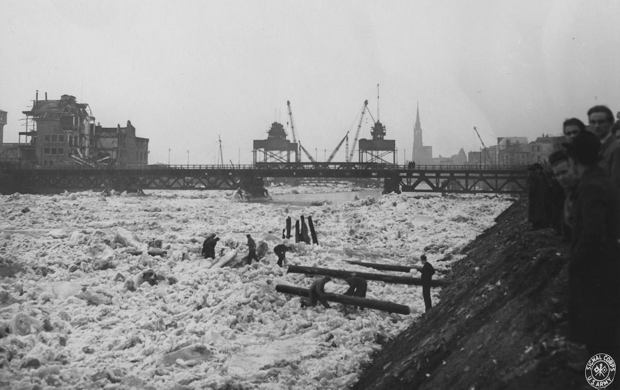Ein Fluss voller Eistrümmer, im Hintergrund eine Brücke, Schwarz-Weiß-Fotografie; Quelle: Staatsarchiv Bremen