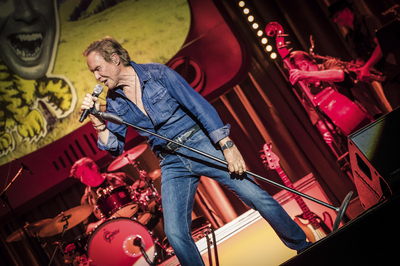 Peter Kraus auf der Bühne mit Mikro in der Hand in Jeans Hemd.