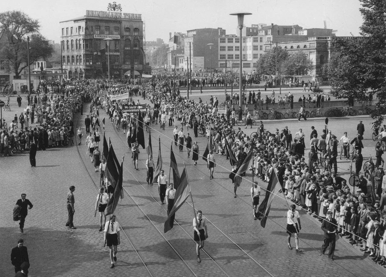 Junge Menschen tragen Fahnen auf einem Umzug, Menschenmassen entlang der Strecke, Schwarz-Weiß-Fotografie; Quelle: Staatsarchiv Bremen