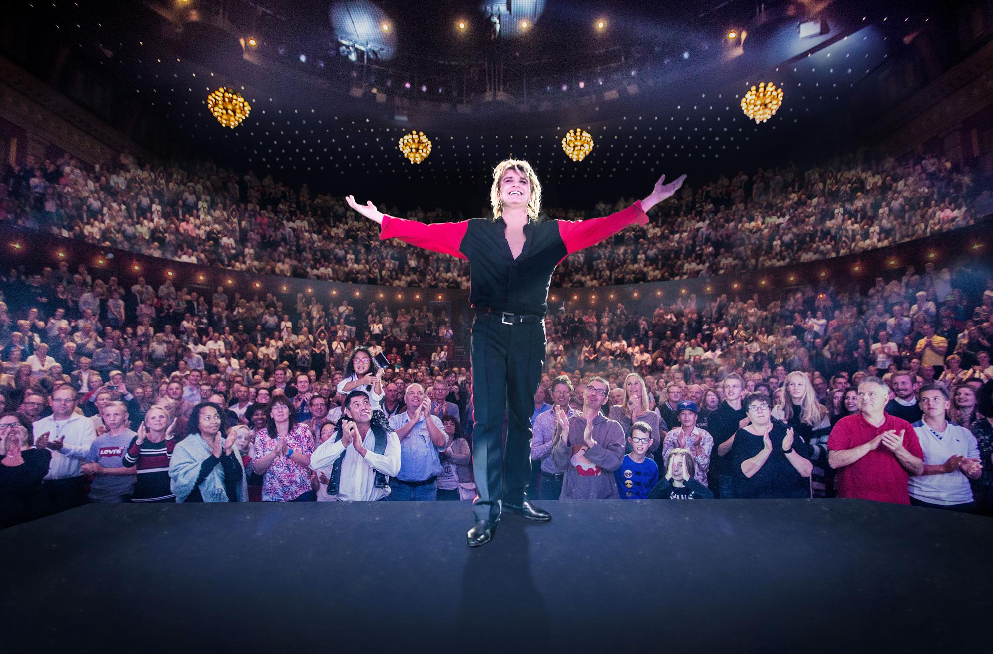 Der Magier Hans Klok steht auf der Bühne mit dem Rücken zum Publikum und man sieht ausverkaufte Ränge.