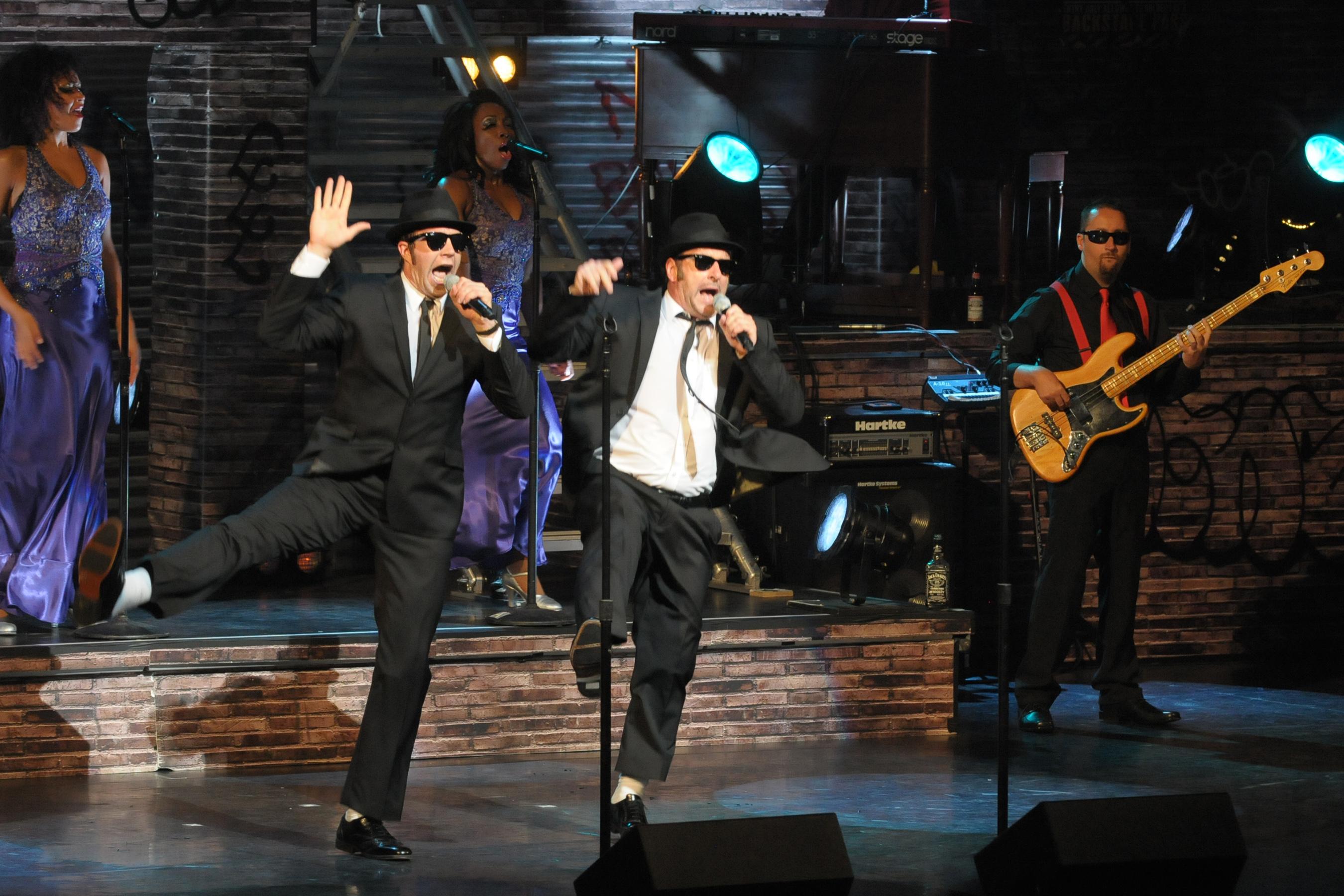 ZWei Musiker stehen in schwarzem Anzug auf der Bühne mit Hut und Sonnenbrille und perfomen.