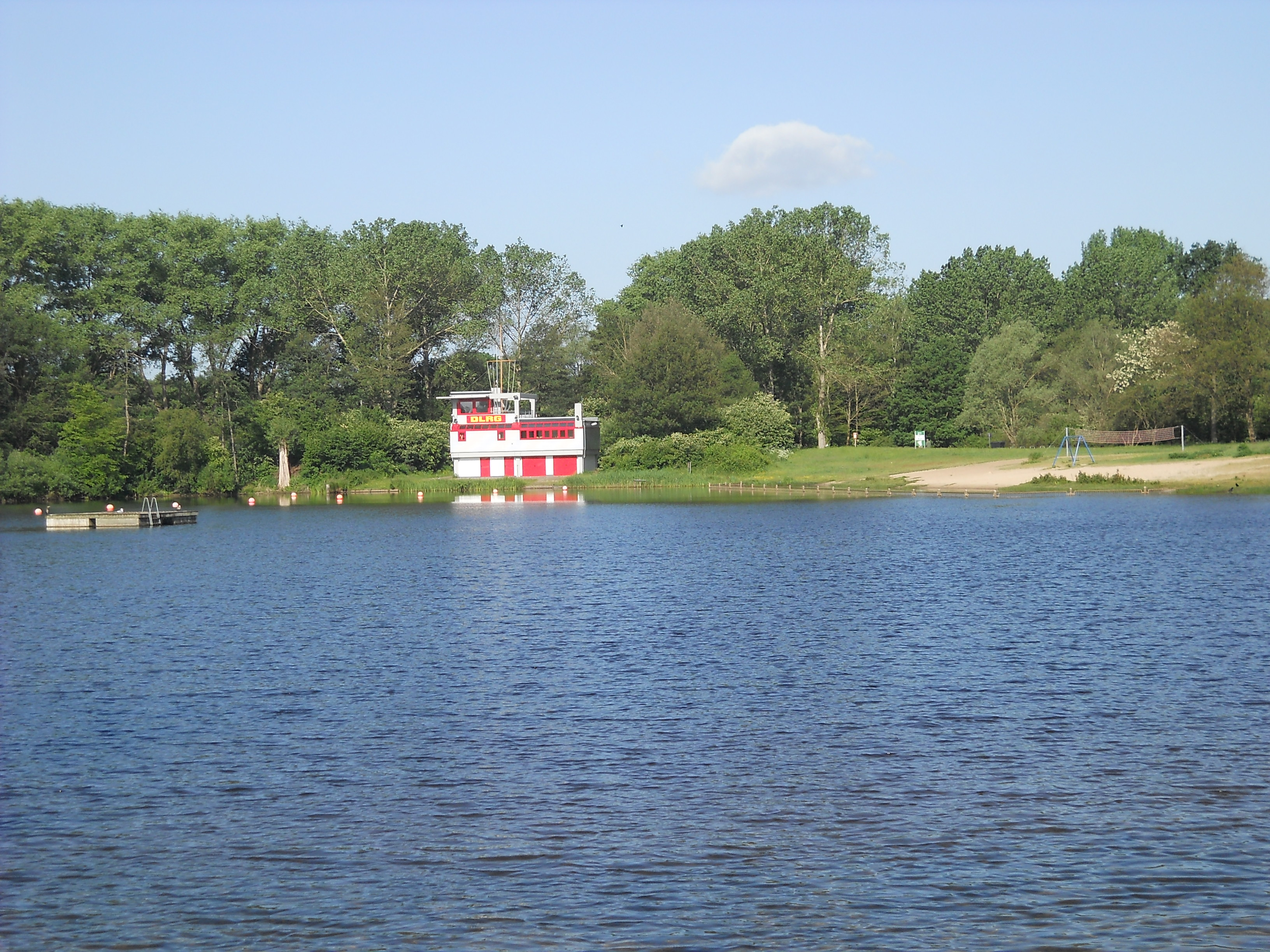 Der Blick über den See zeigt am gegenüberliegenden Ufer die Station der DLRG