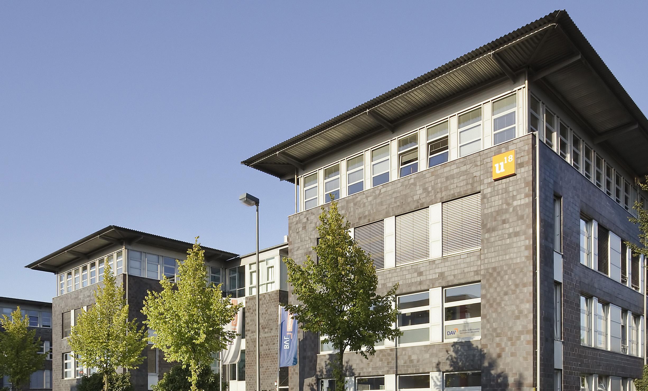 Gebäude der IUBH im Ausschnitt mit Bäumen; Quelle: Bundesvereinigung Logistik (BVL)