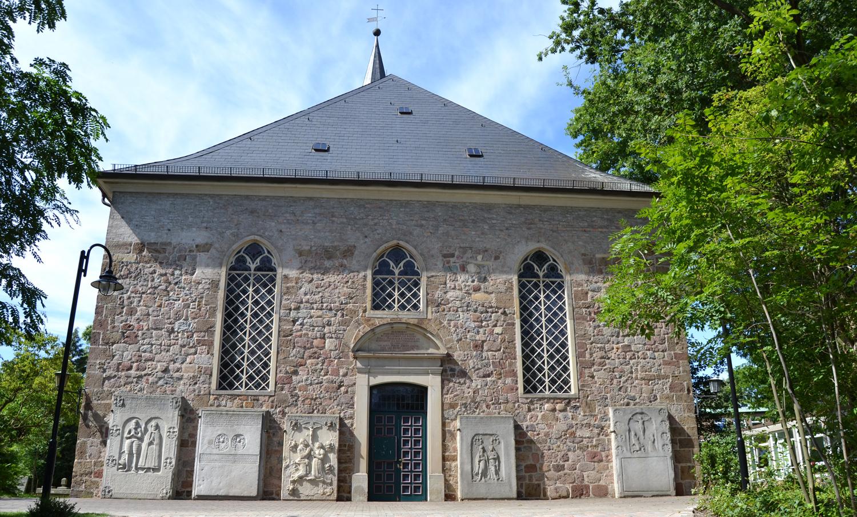 Ein großes Kirchengebäude mit Bäumen rechts und links.