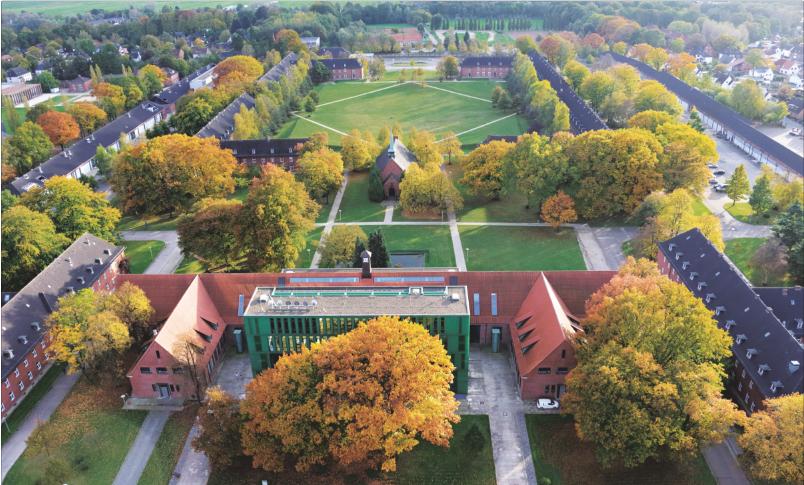 Eine Luftaufnahme zeigt Kasernen-Gebäude umgeben von herbstlich gefärbten Bäumen; Quelle: Jacobs University Bremen