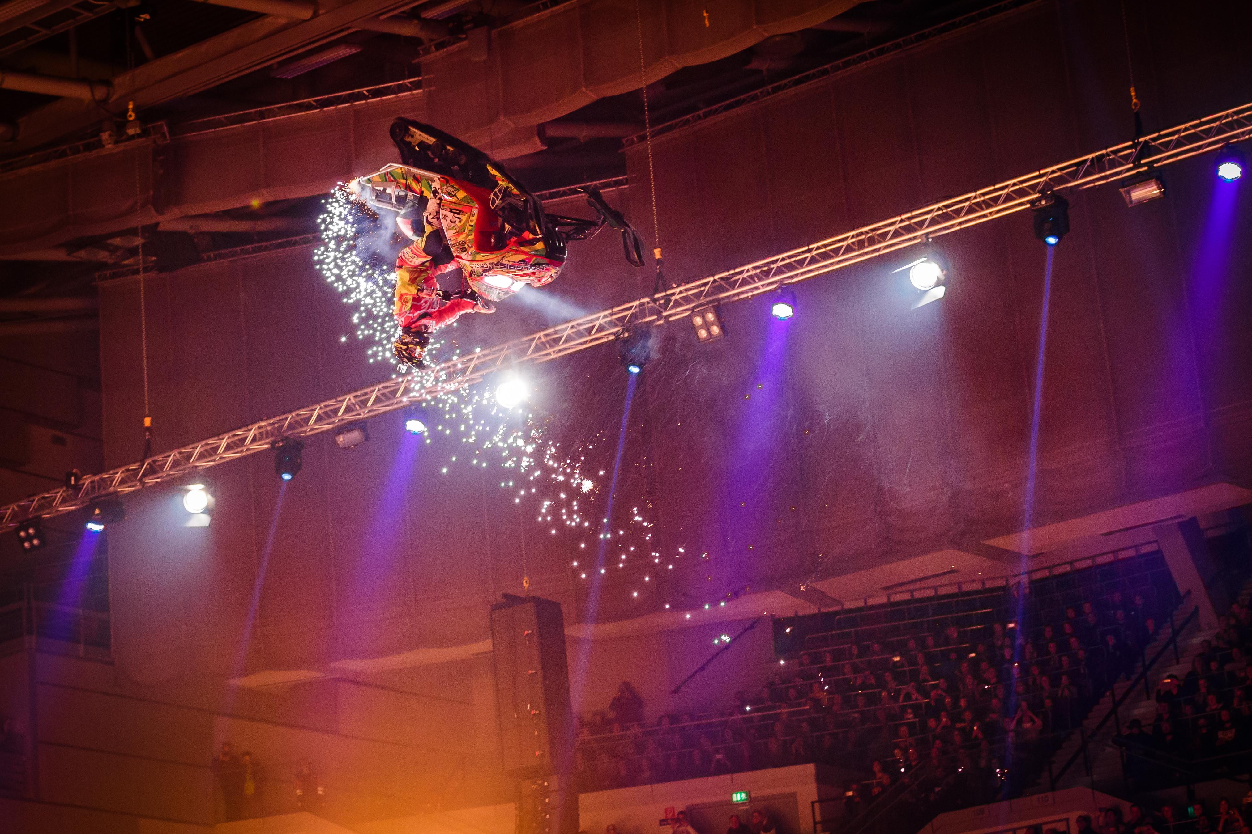 Ein Extremsportler bei der Night of Freestyle macht einen Salto mit einem Motorrad.