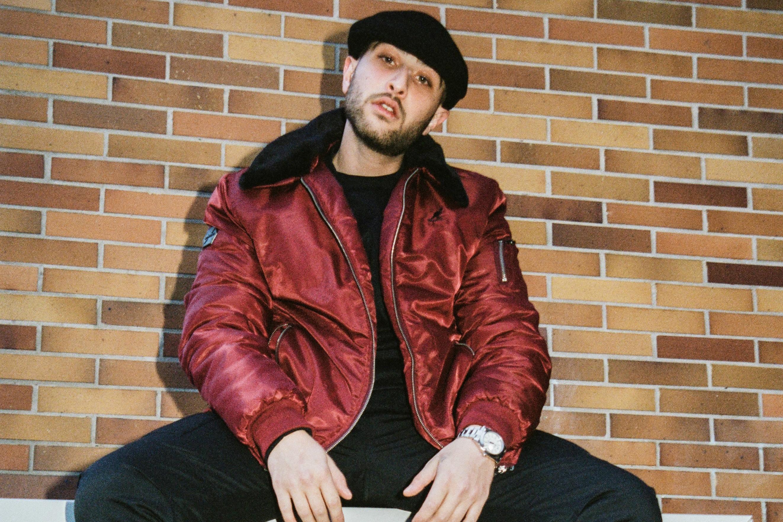 Rapper Nimo sitzt auf einer Metalltruhe in einem dunkelrotem Blazer und einer schwarzen Mütze und schaut in die Kamera.