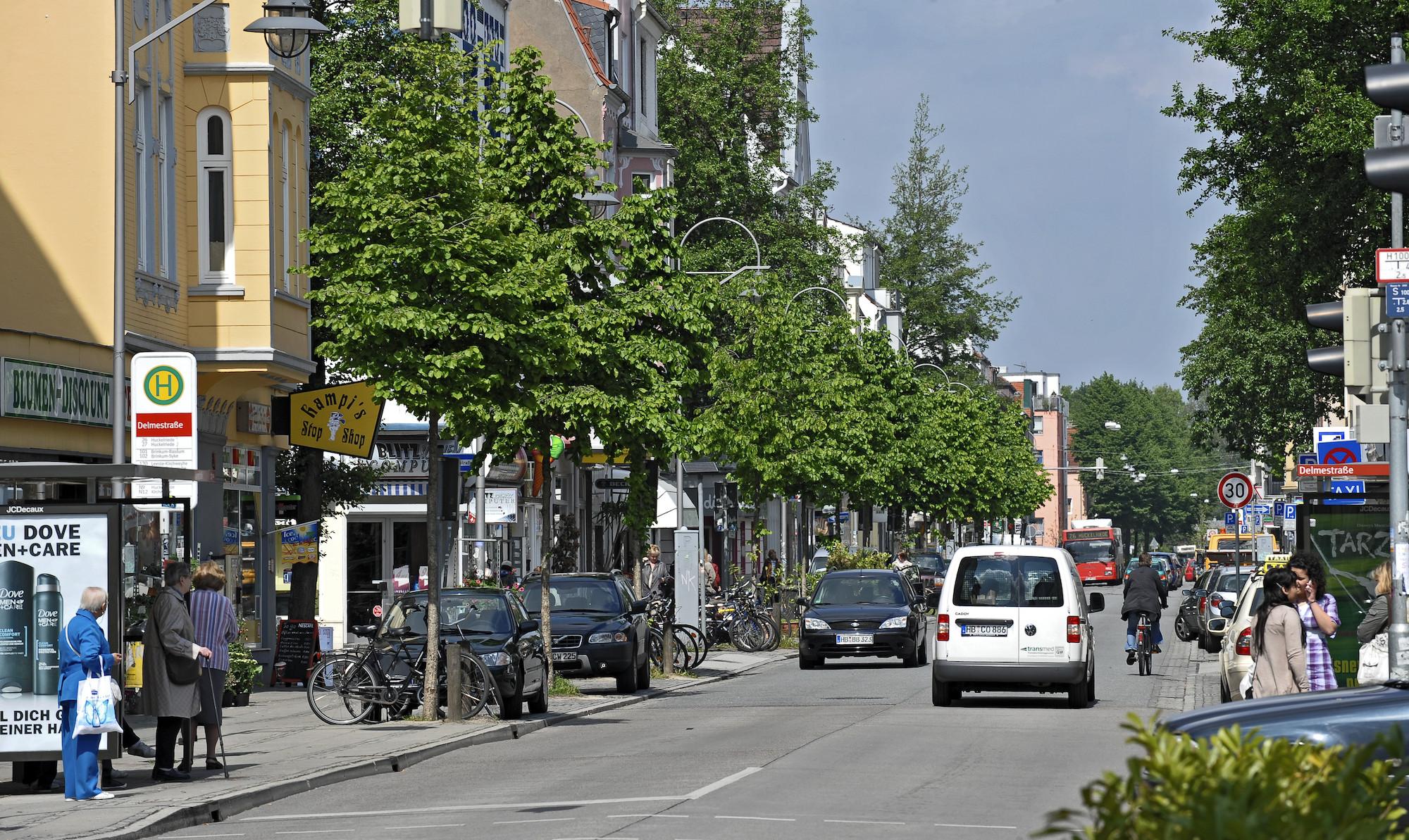 Ein Straßenzug, befahren von zwei Autos und einem Fahrrad, links eine Bushaltestelle; Quelle: WFB/Frank Pusch