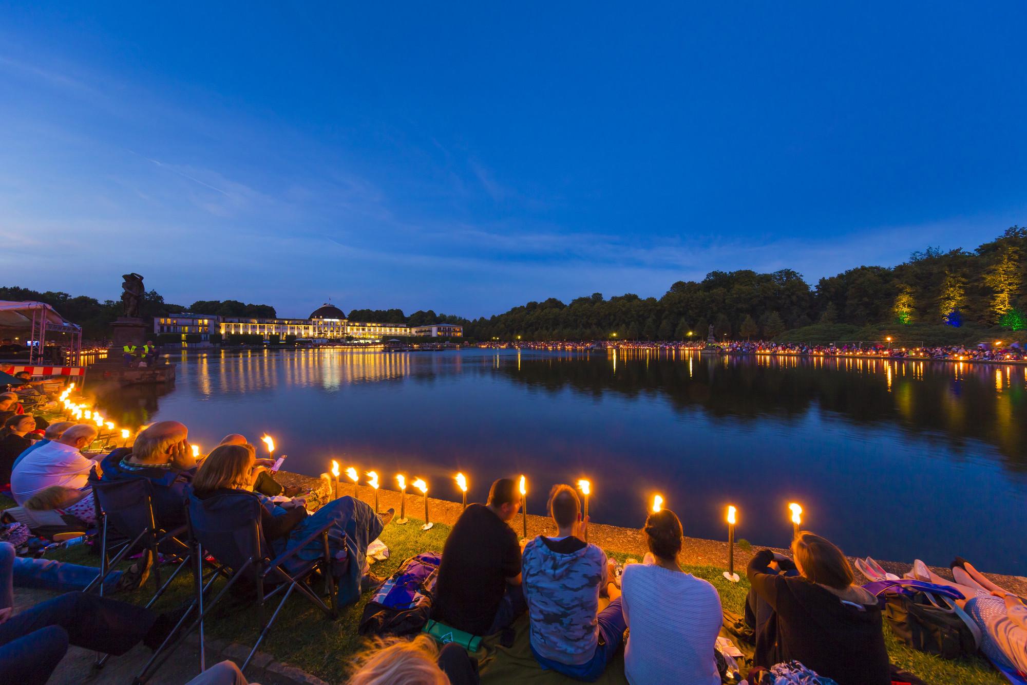 Menschen sitzen mit Picknickdecken um den Hollersee und lauschen einem klassischen Konzert