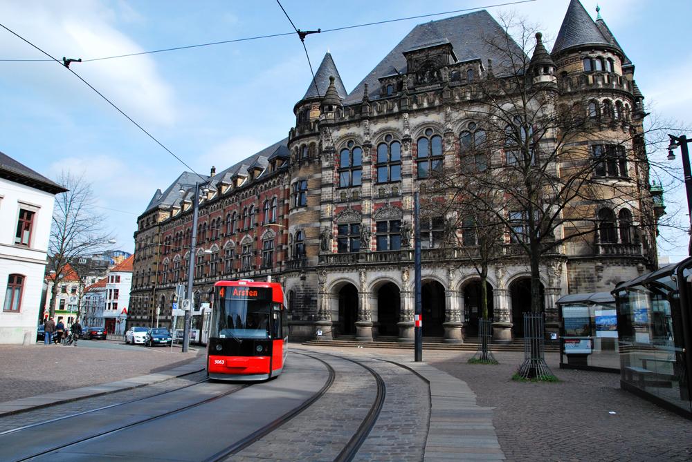 Eine Straßenbahn fährt Richtung Domsheide, im Hintergrund das Landesgericht