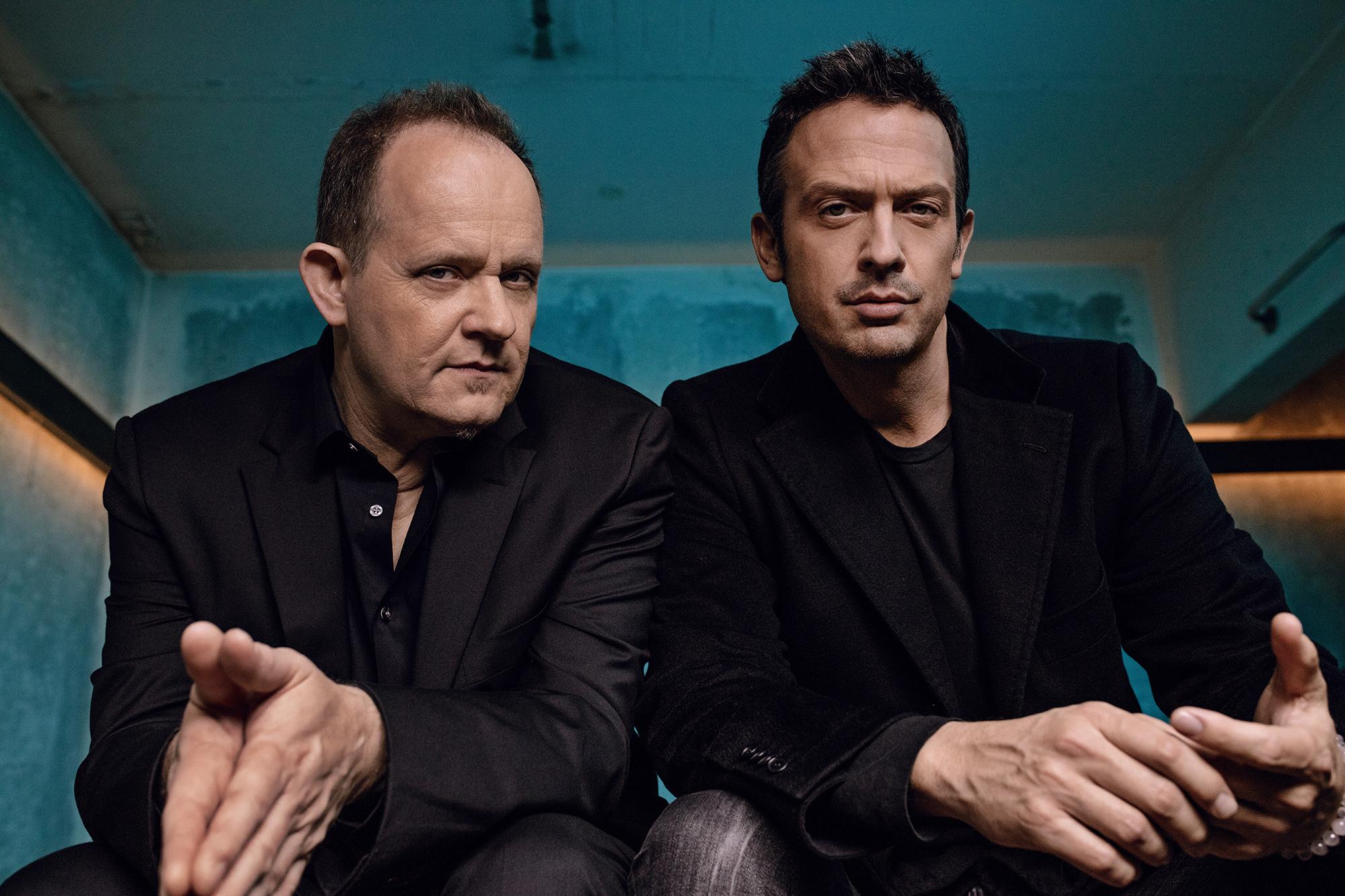 Till Brönner sitzt mit einem Kollegen in einem schwarzen Mantel und einem dunklen T-Shirt und schaut mit gefalteten Händen in die Kamera.
