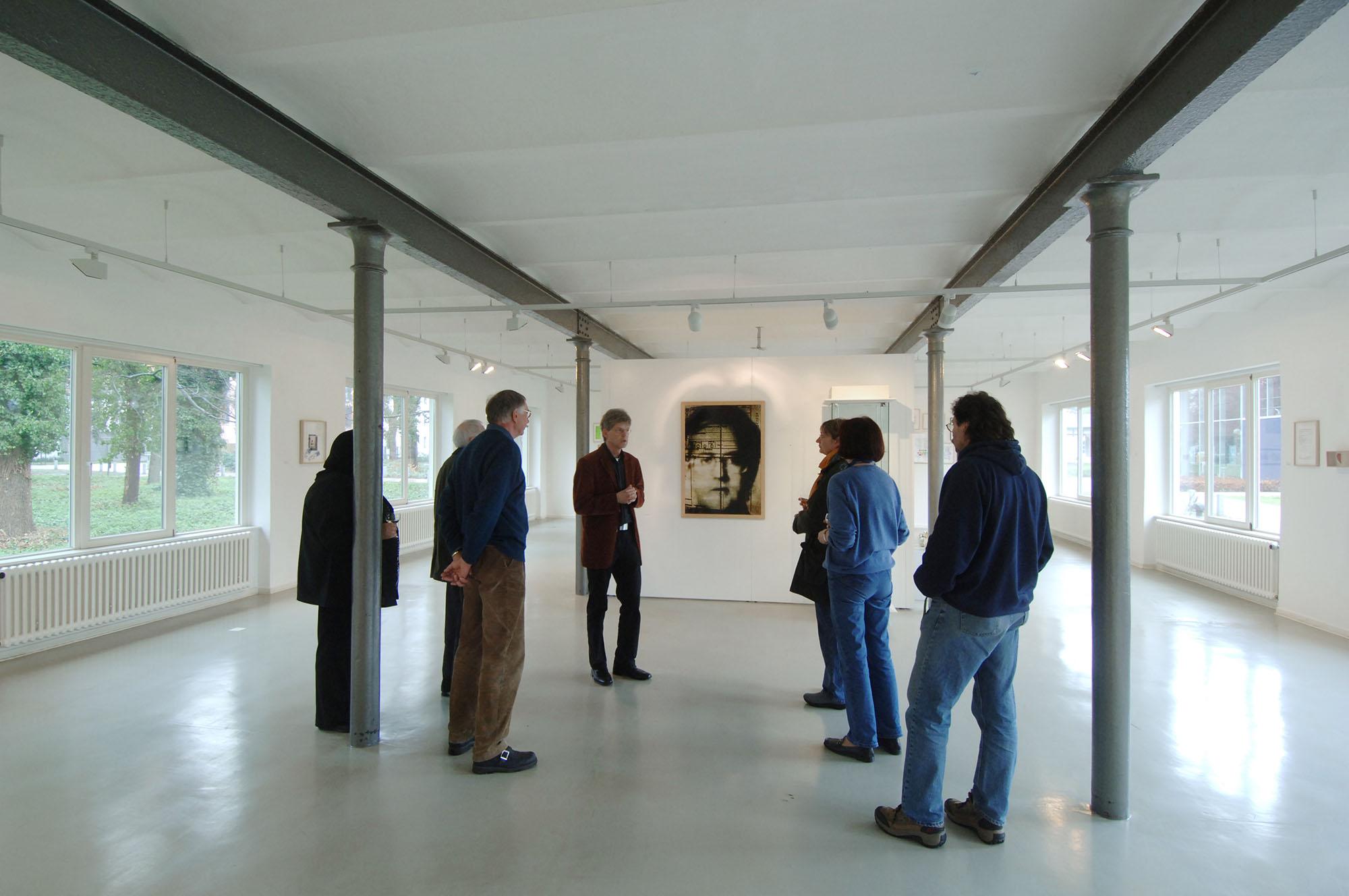 Eine Innenaufnahme der Galerie im Park. Ein heller weißer Raum mit dunklen Holzbalken und einer Gruppe Besucher.