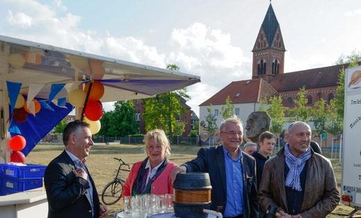 """Eine Menschengruppe steht um einen Stehtisch im Freien zur Eröffnung der """"Hemelinger Vielfalt""""."""