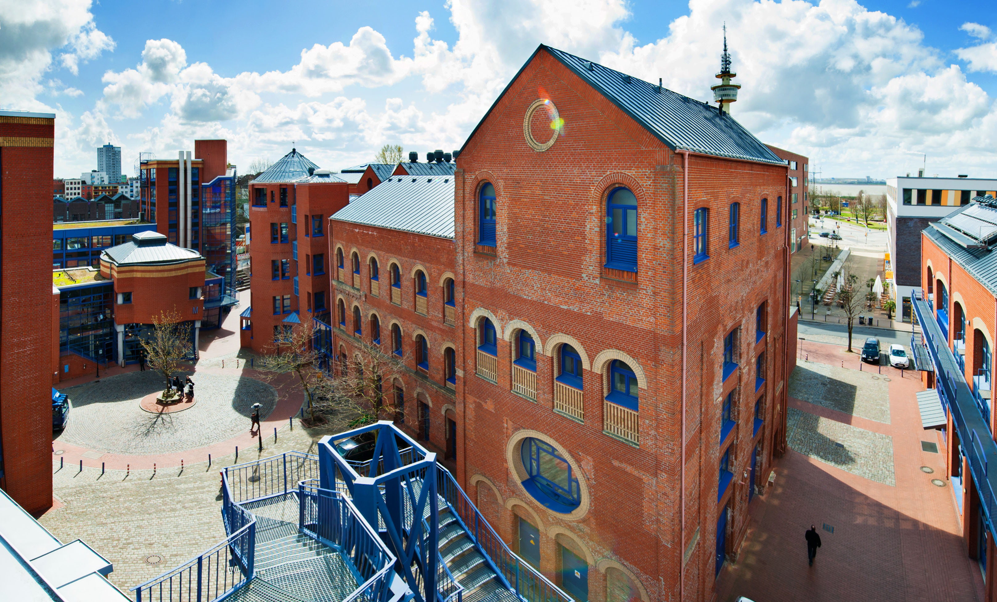 Ein rotes Backsteingebäude, im Vordergrund eine große blaue Metalltreppe; Quelle: Thilo Vogel