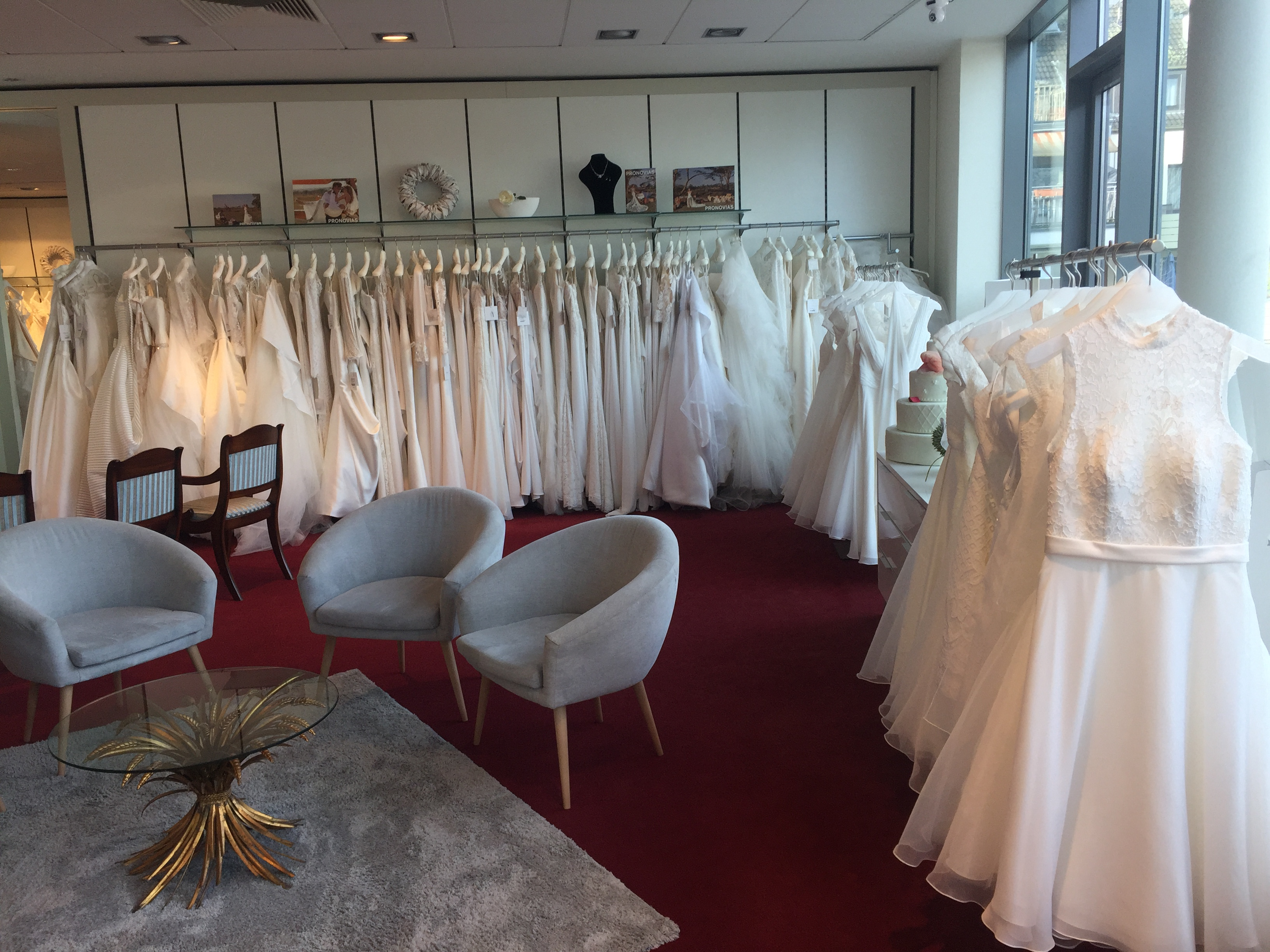 Weiße Brautkleider hängen an Stangen, auf dem Boden roter Teppich