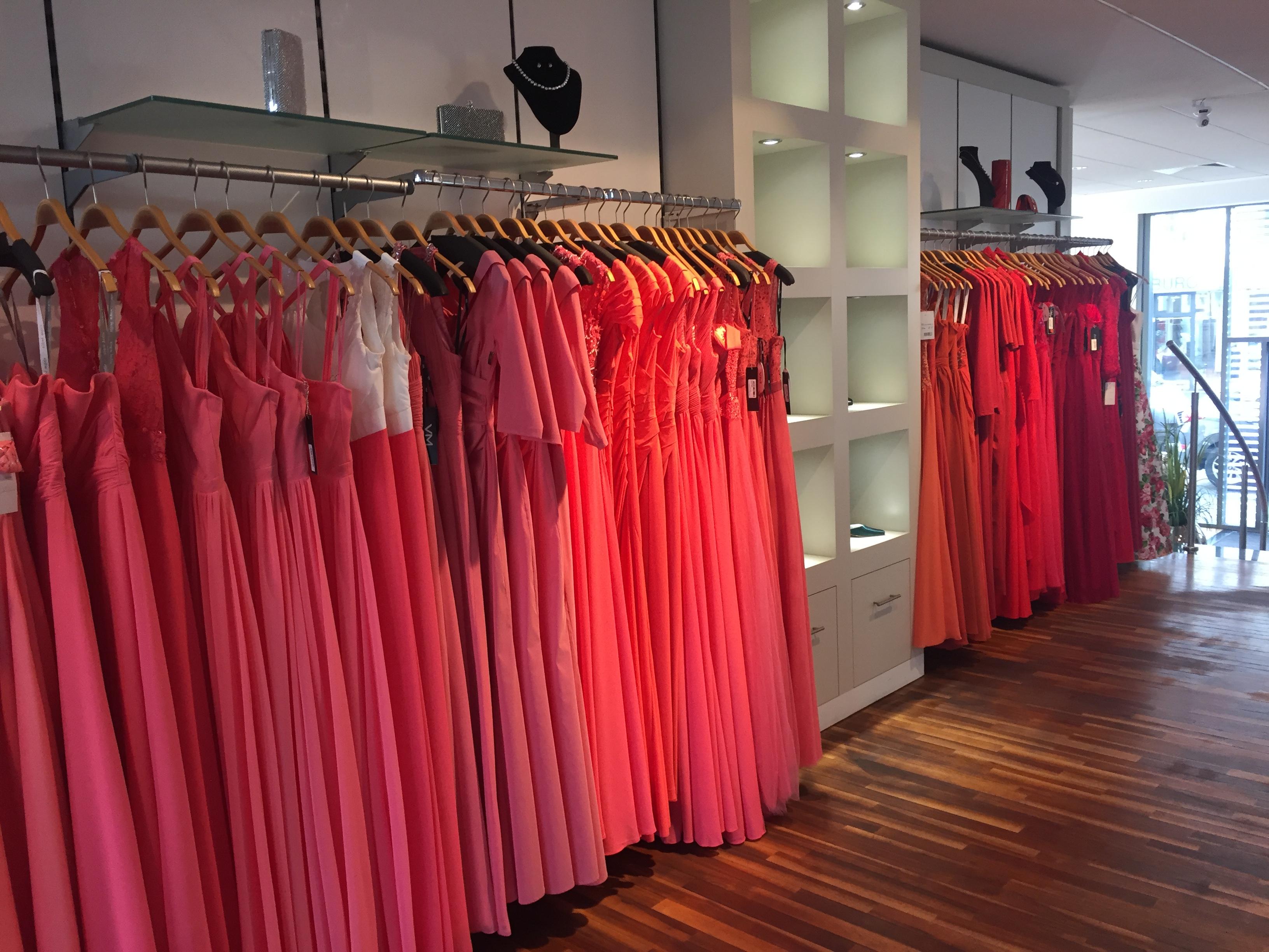 Lange Kleider in unterschiedlichen Rottönen hängen an einer Stange