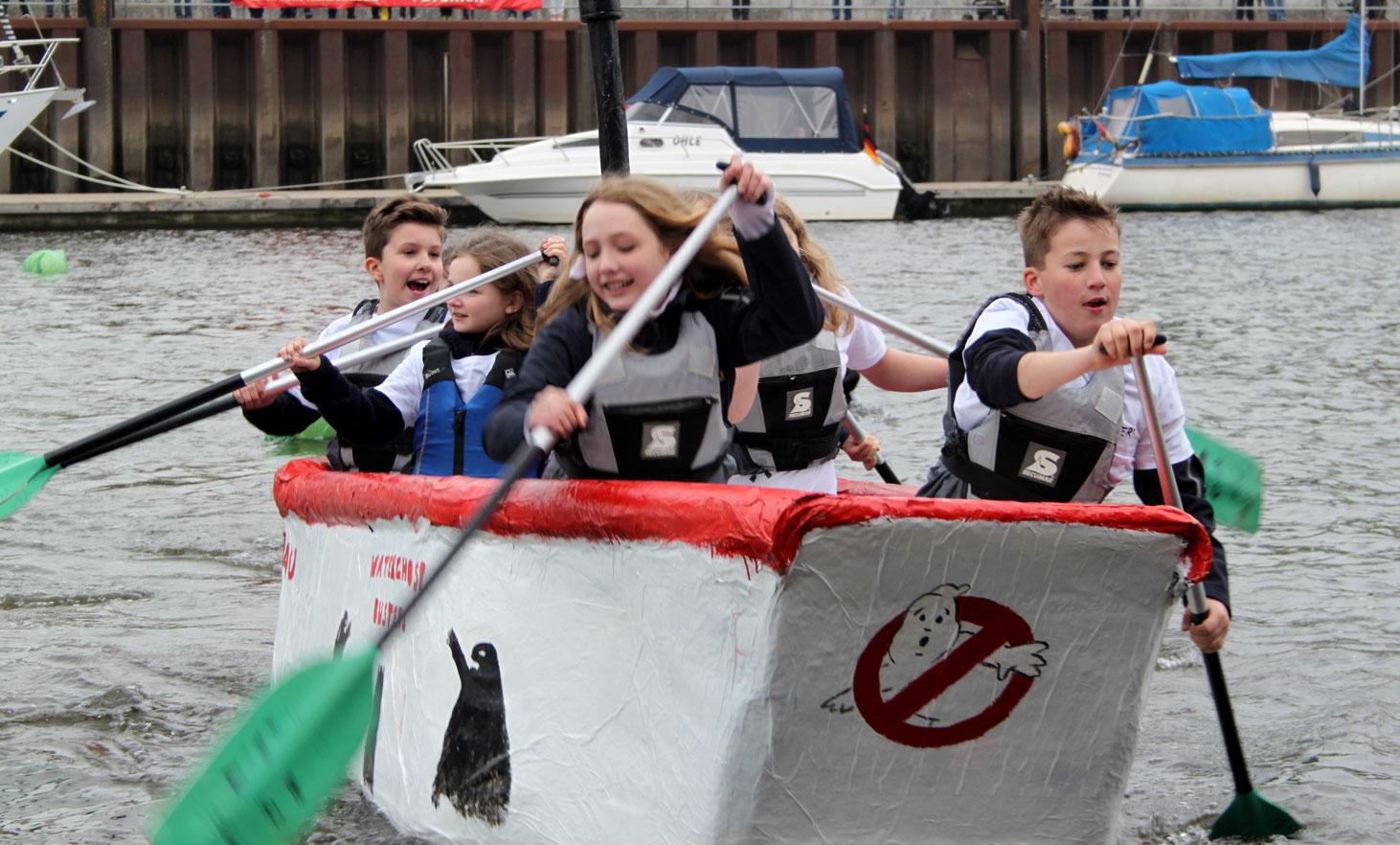 Kinder in ihrem Pappboot auf dem Wasser.