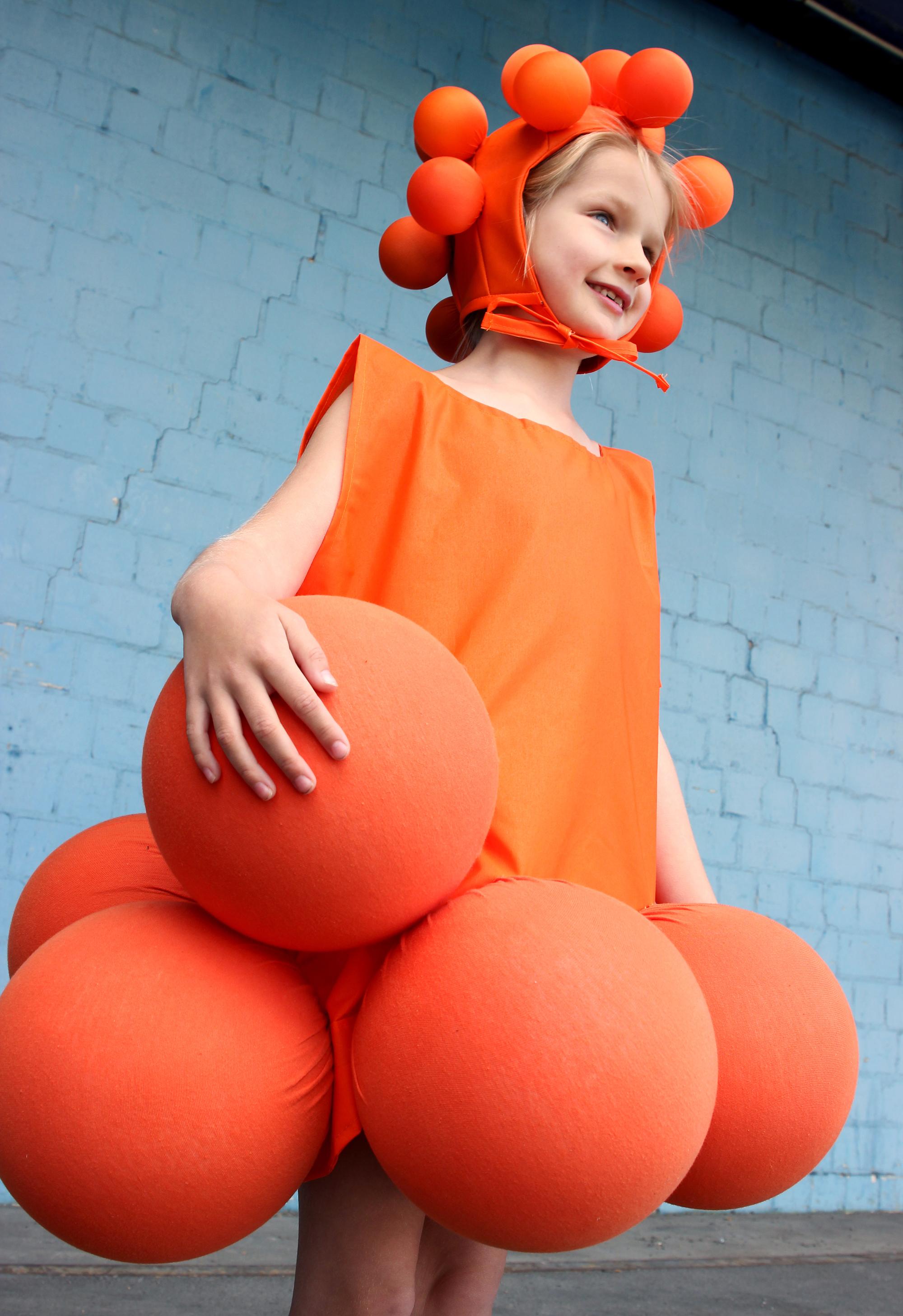 Ein Mädchen ist prunkvoll in einer orangenen Verkleidung.