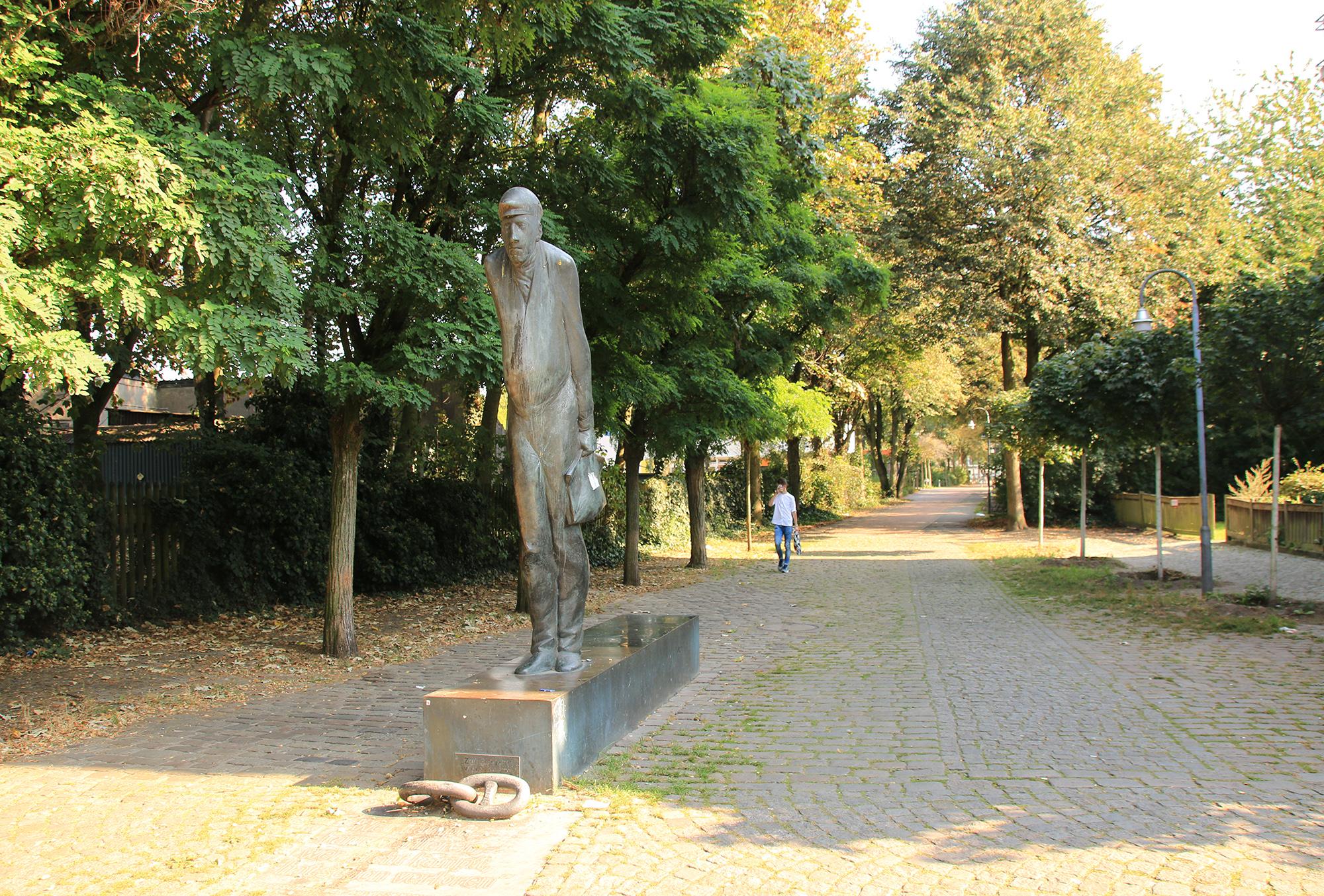 Die Bronze-Skulptur Zur Schicht steht in Gröpelingen an der Lindenhofstraße, Ecke Dockstraße.