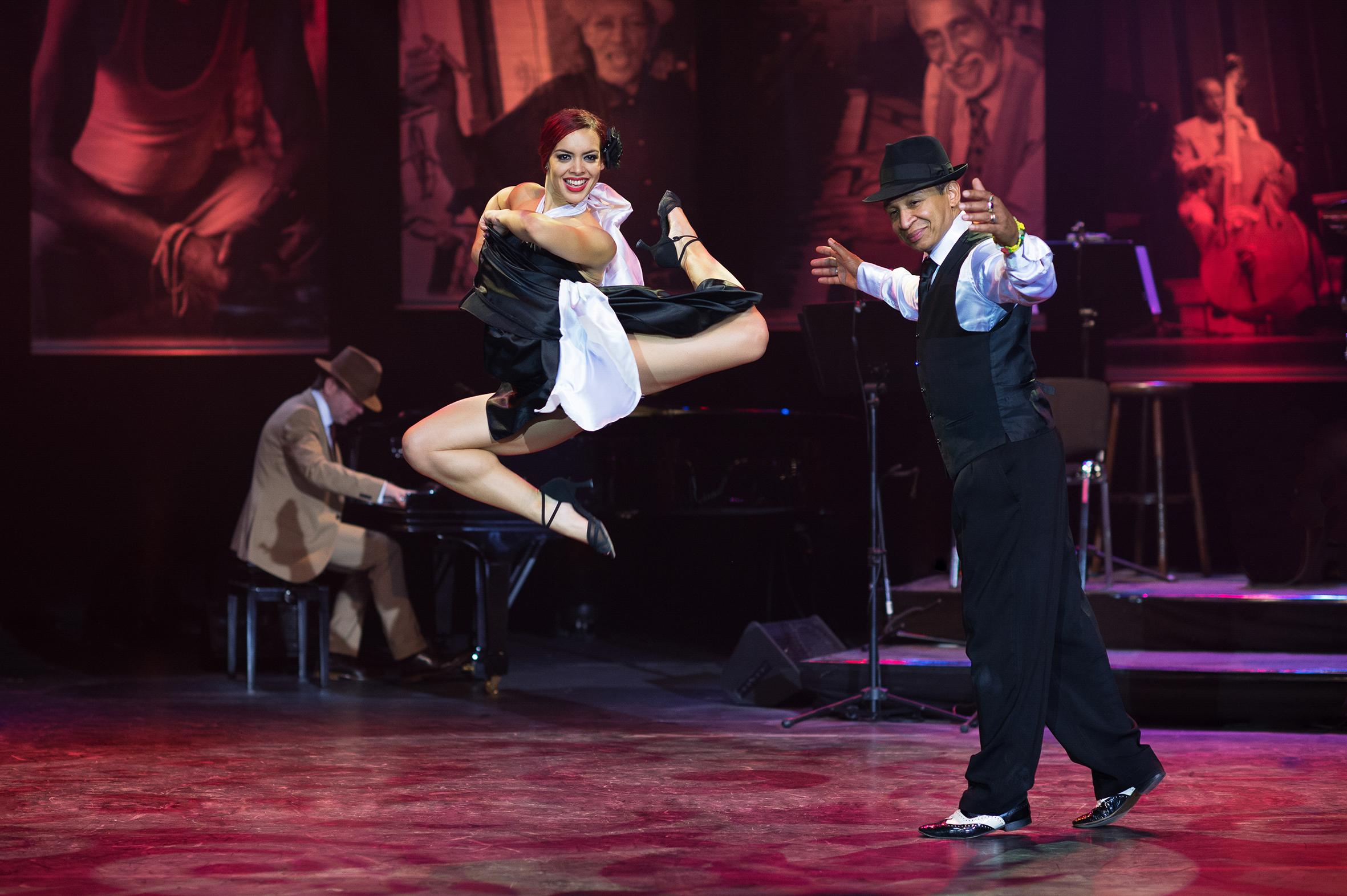 Zwei Tänzer auf der Bühne eine Frau springt spektakulär hoch und der Herr schaut amüsiert zu.