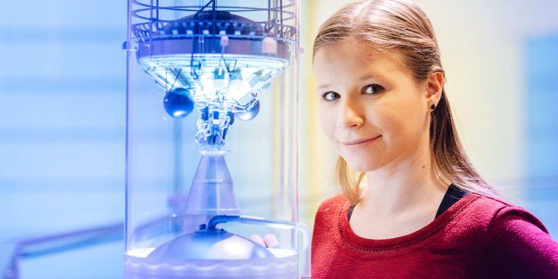Eine Frau in rotem Pullover neben einem Satellitenmodell.