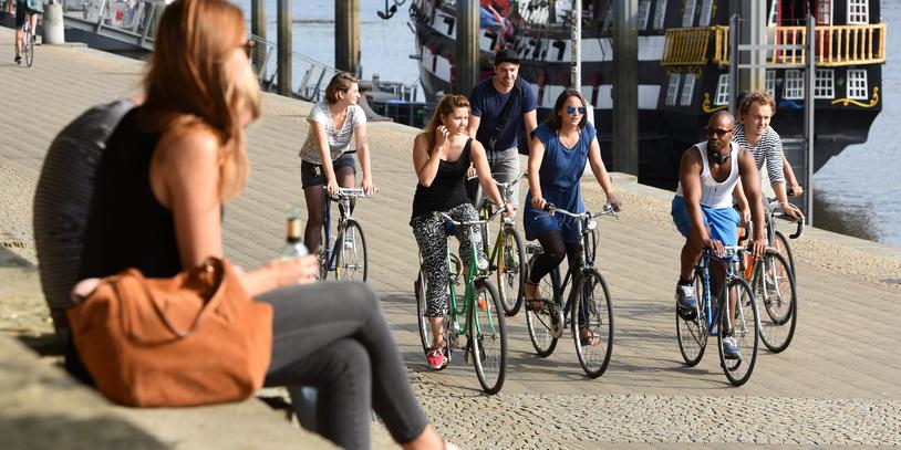 Menschen sitzen auf den steinernen Stufen an der Schlachte in der Sonne, Radfahrer fahren vorbei.