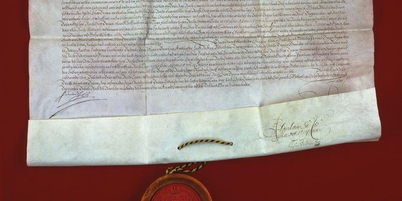 Ein altes Schriftstück mit einem Siegel auf rotem Untergrund