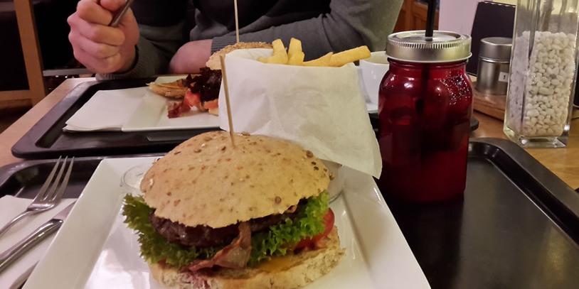 Burger und Limonade in einem roten Gefäß, auf schwarzem Tablett.