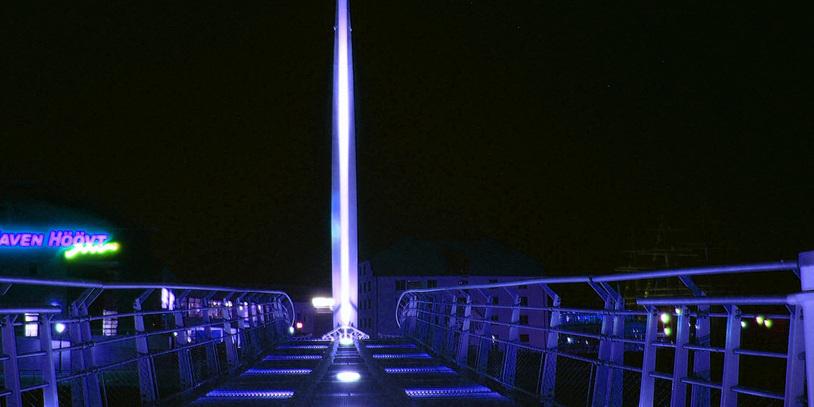 Eine silberne Brücke mit blauen Lichtern bei Nacht.