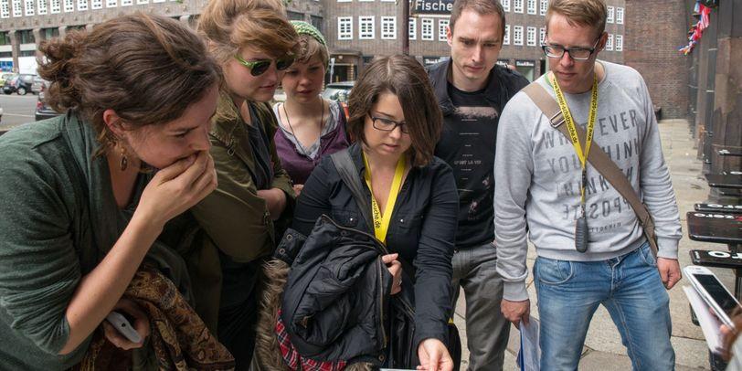 """Sechs Teilnehmer der """"Städte Schatzsuchen"""" schauen konzentriert auf eine Karte."""