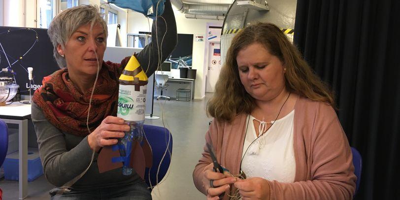 Zwei Frauen sitzen an einem Tisch und basteln eine Rakete aus einer Wasserflasche.