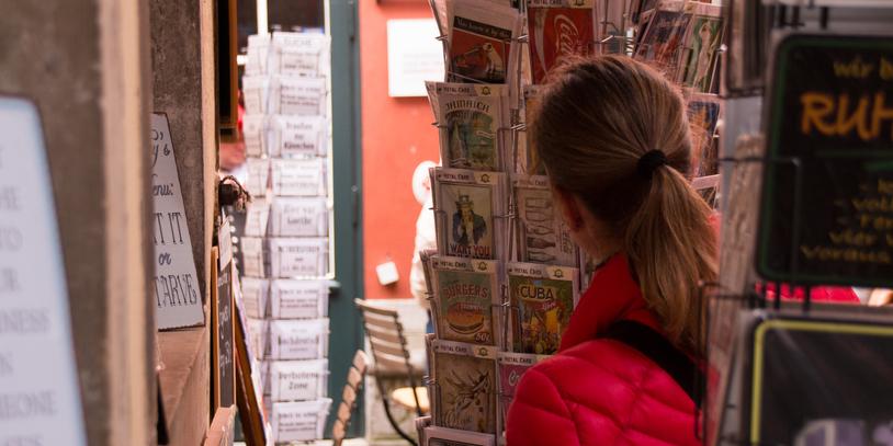 Ein Geschäft mit Kartenständern, an denen gerade ein Frau die Karten begutachtet.