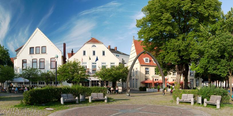 Gepflasterter Platz umrahmt von Häusern und Bäumen