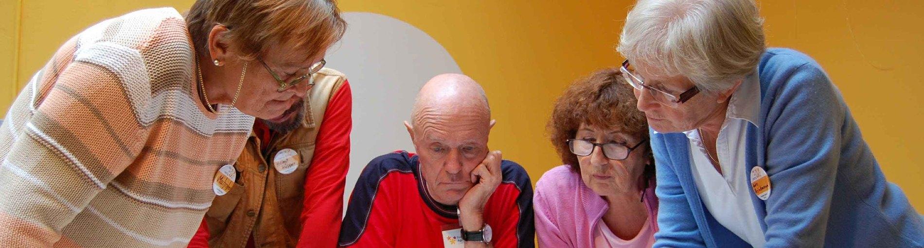 Mehrere Menschen schauen im Halbkreis auf ein Papier auf dem Tisch; Quelle: Freiwilligen-Agentur Bremen/Frank Mayer