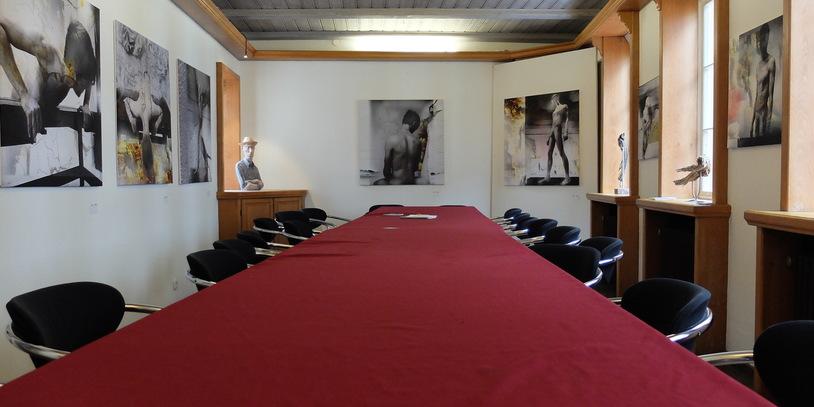 Blick auf eine lange Tafel mit roter Tischdecke und schwarzen Stühlen. An den Wänden des Raumes befinden sich große Fotografien.