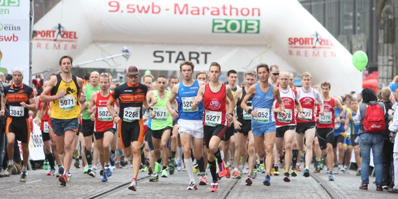 Teilnehmer eines Marathons laufen am Start los.