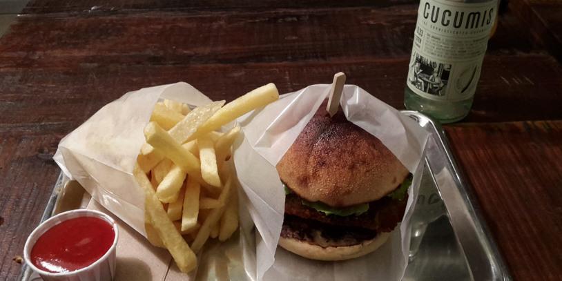 Burger-Menü mit Pommes und Getränk auf Metalltablett.