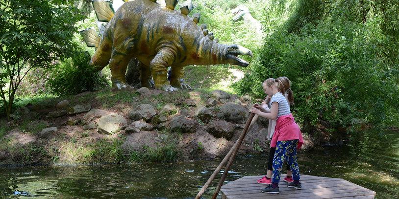 Zwei Mädchen führen ein hölzernes Floß, im Hintergrund das Modell eines Dinosauriers am Ufer.