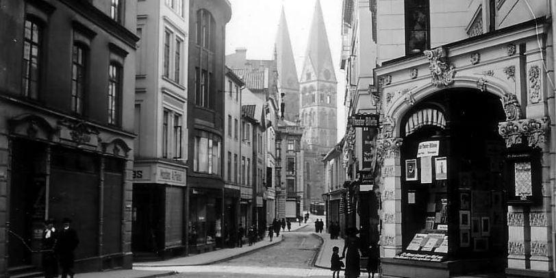 Eine schwarz-weiß Abbildung zeigt eine Straße, die von Gebäuden gesäumt ist. Rechts ist ein Eingang mit Warenauslage im Schaufenster zu sehen. Am Ende der Straße sind zwei spitze Türme zu sehen. Vereinzelt laufen Menschen durch die Straße.