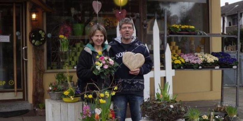 Die Inhaber stehen vor ihrem Blumengeschäft und lächeln in die Kamera.
