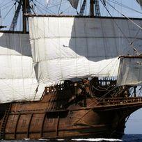 Ein Zweimaster mit gehissten, weißen Segeln auf dem offenen Meer und einer Spanien Flagge.