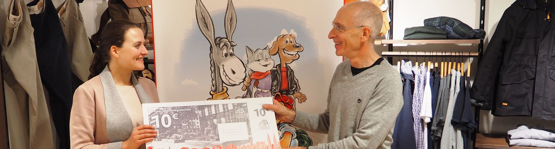 Links steht eine Frau und rechts ein Mann die zusammen einen Bremer Geschenkgutschein halten.