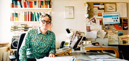 Ein Mann sitzt an einem Schreibtisch, vor ihm ein Laptop, im Hintergrund ein Bücherregal; Quelle: WFB/Jonas Ginter<br />