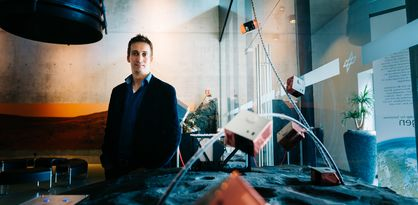 Ein Mann im Sakko und Hemd lacht in die Kamera, im Hintergrund ein großes Glasfenster; Quelle: WFB/Jonas Ginter