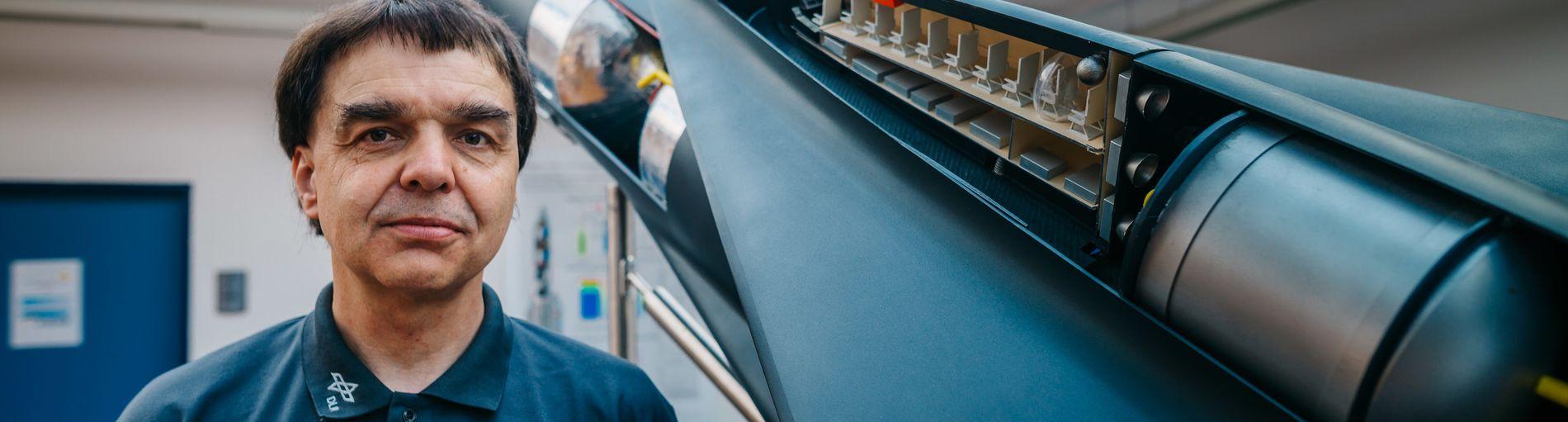 Ein Mann in einem blauen Hemd steht neben dem Modell einer Rakete; Quelle WFB/Jonas Ginter