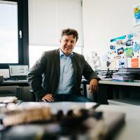 Ein Mann sitzt auf einem Stuhl in einem Büro, im Vordergrund Computer-Platinen; Quelle: WFB/Jonas Ginter