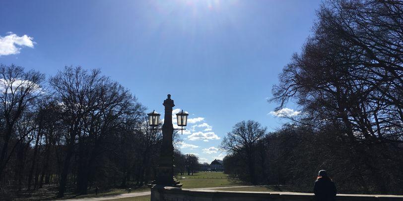 Zu sehen ist das Geländer einer Brücke, eine Frau, die daran lehnt sowie eine Laterne links von der Brücke. Rechts und links säumen Bäume das Bild. Die Sonne steht hoch am blauen Himmel und im Hintergrund sind grüne Wiesen zu erkennen.