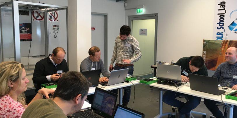 Eine Gruppe Menschen sitzt im DLR_School_Lab an u-förmig aufgestellten Tischen an ihren Laptops. Ein Mann steht daneben und erklärt ihnen etwas.